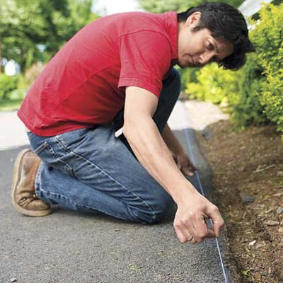 Mark Powers secures a chalk line on the edge of a driveway