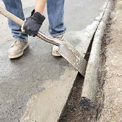 man prying a spade between asphalt that's been cut and the excess asphalt