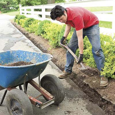 Mark Powers digs a trench next to an asphalt driveway