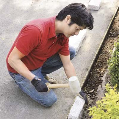 Mark Powers installing edging blocks with a rubber mallet