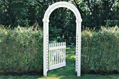 arched garden arbor standing between hedges on a lawn