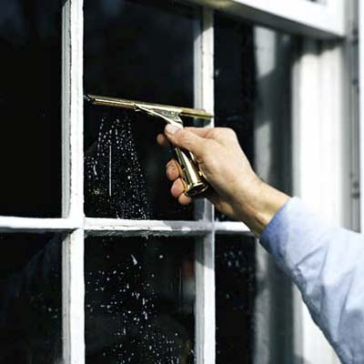 man using a customized squeegee to wipe soapy water from smaller panes of glass