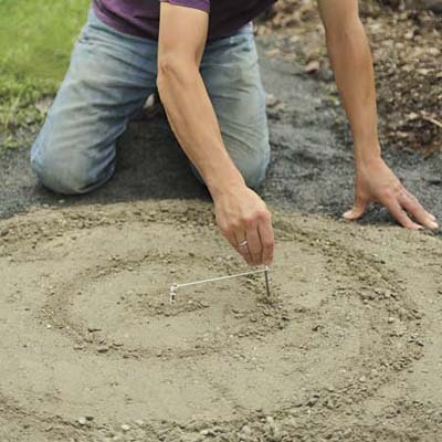 Mark Powers marking out the radius of his pebble mosaic with two nails attached to a piece of string