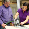 Tom Silva and Amy Paladino use a router to make [FRACTION 12]-inch slots for plywood shelves