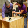 Tom Silva and Amy Paladino assemble the base of the tool bench