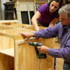 Tom Silva and Amy Paladino install furring strips in order to mount the pegboard on the side of the tool bench