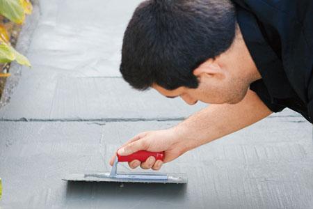 man trowels concrete resurfacer onto a concrete walkway