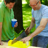 man using handsaw to cut grooves on kubb pieces