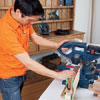 Mark Powers uses a miter saw to cut pieces for a bar cart