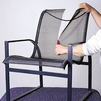 man slashing old mesh chair sling