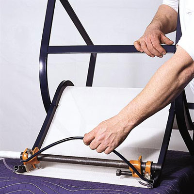 man reinserting spreader bar of patio chair with replaced sling