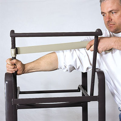 man stretching a vinyl strap across outdoor patio chair frame