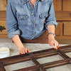 woman prepares salvaged window sash
