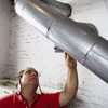 man inspecting flue pipe of furnace