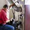man adjusting furnace burner and testing efficiency