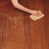 hand sanding wood floor in preparation for painting