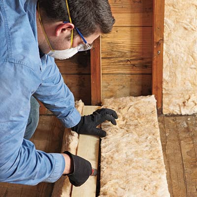 man cutting insulation batting