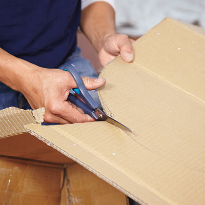 man cutting out cardboard template for wall niche installation