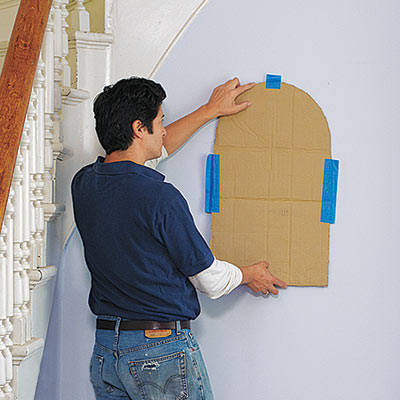 man placing wall niche template on wall