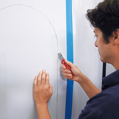 man using utility knife to cut wall for wall niche installation