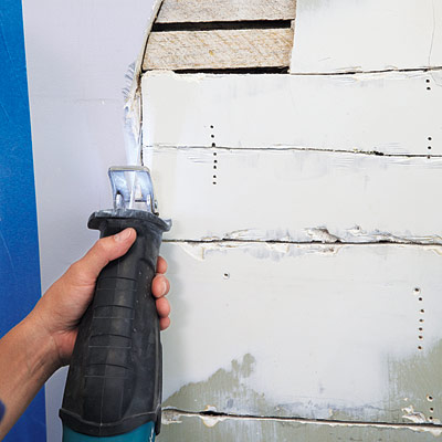 man using reciprocating saw to remove lath and plaster for wall niche installation