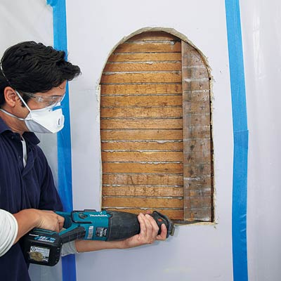 man sawing stud out of wall for wall niche installation