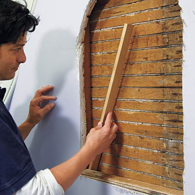 man installing additional padding for wall niche installation