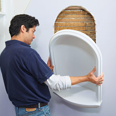 man setting wall niche in place