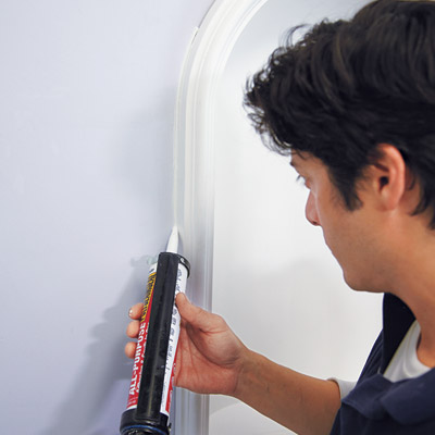 man caulking perimeter of wall niche