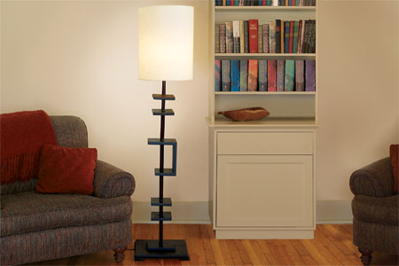 lamp made from a curtain rod standing lit in a room