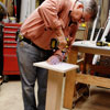 Tom Silva attaches a leg plate to the table leg for a trestle table with a drill/driver
