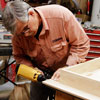 Tom Silva attaches 1/4-inch trim to the edges of the table top for a trestle table