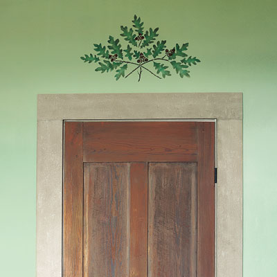 an oak-branch motif stencil above a door
