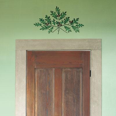 an oak-branch motif stencil above a door