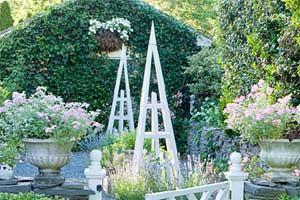 pyramid trellis installed in a beautiful yard filled with plants and flowers