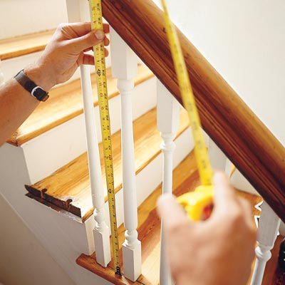 using a tape measure to measure the length of a baluster on a stairway