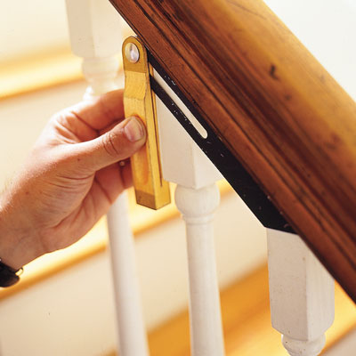 using a T-bevel to measure the top angle of the railing on a stairway