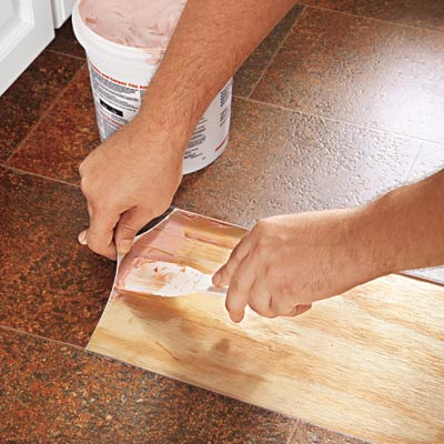 using a putty knife to lift up edges of vinyl flooring patch area