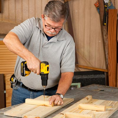 Tom Silva attaching a 2x2 to 2 1x6 side boards with a drill/driver