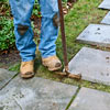 using a half-moon edger to cut around base of each paver in stone stepping path