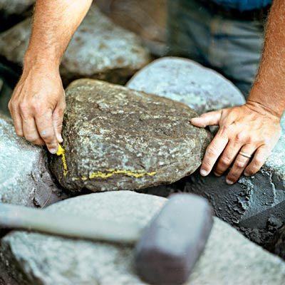 marking stones to cut for building a fieldstone wall