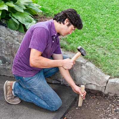 checking the depth of an area of removed driveway