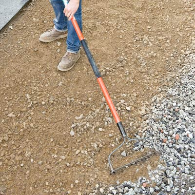 raking leveling sand into an area of removed driveway