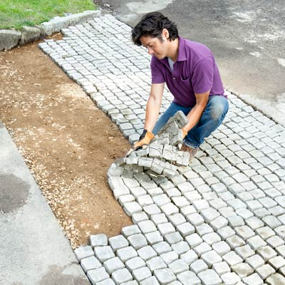 laying more cobblestone mats in the driveway apron