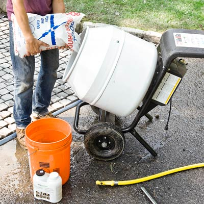 mixing grout to add between a cobblestone driveway apron