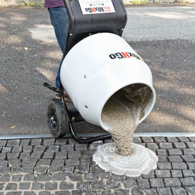 spreading grout onto a cobblestone driveway apron