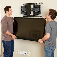 two men hanging a flat-screen TV on a wall