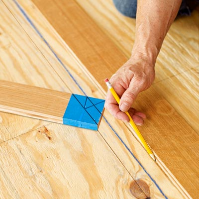 marking the subfloor for a herringbone floor using the marked wood slat