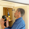 attaching the hardwood frame with crown molding to the kitchen cabinets