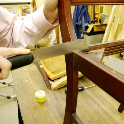 cutting off a chair-front with a flush-cut pull saw